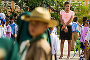 11 JULY 2013 - PATTANI, PATTANI, THAILAND:   A Buddhist teacher at the Bantaladnadklongkud School in Pattani walks among her students. One of the things Muslim parents object to is the way the Buddhist teachers dress. The want the teachers to dress more modestly and to show more respect to Muslim traditions. There are 108 students at Bantaladnadklongkud School and they are all Muslims. Five of the school's eight teachers are Buddhists.    PHOTO BY JACK KURTZ
