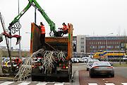 Auto's rijden over het fietspad omdat de weg is geblokkeerd door een vrachtwagen. Vanuit de vrachtwagen worden bomen gepland.<br /> <br /> Cars are riding on the bicycle path to pass a truck.