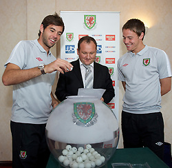 CARDIFF, WALES - Tuesday, August 31, 2010: Wales' Joe Ledley draws out a ball for the Welsh Cup draw with FAW Head of Competitions Andrew Howard and Chris Gunter at the Vale of Glamorgan Hote;. (Pic by David Rawcliffe/Propaganda)