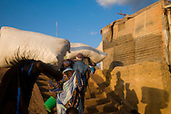 Men unloading  boat in Mopti's harbour. At the confluence of the Niger and the Bani rivers, between Timbuktu and Ségou, Mopti is the second largest city in Mali, and the hub for commerce and tourism in this west-african landlocked country.
