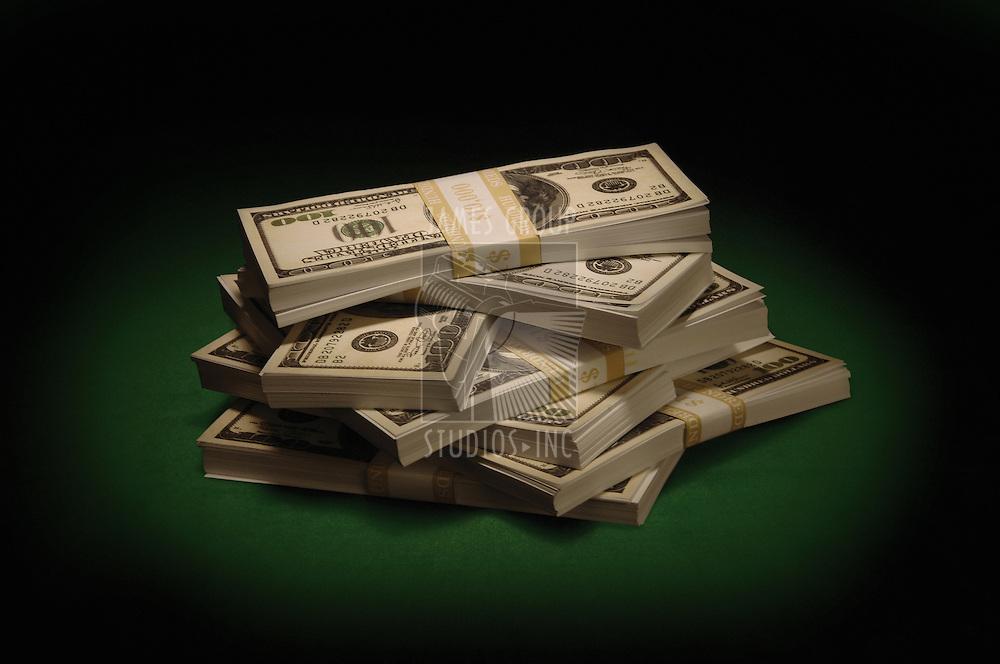 Piles of US $100 bills on green felt under a spotlight