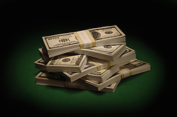 Piles of US $100 bills on green felt under a spotlight