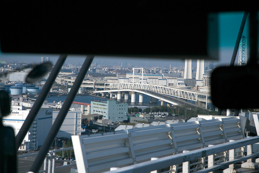 person in bus traveling looking out over Tokyo bay with a large bridge in view