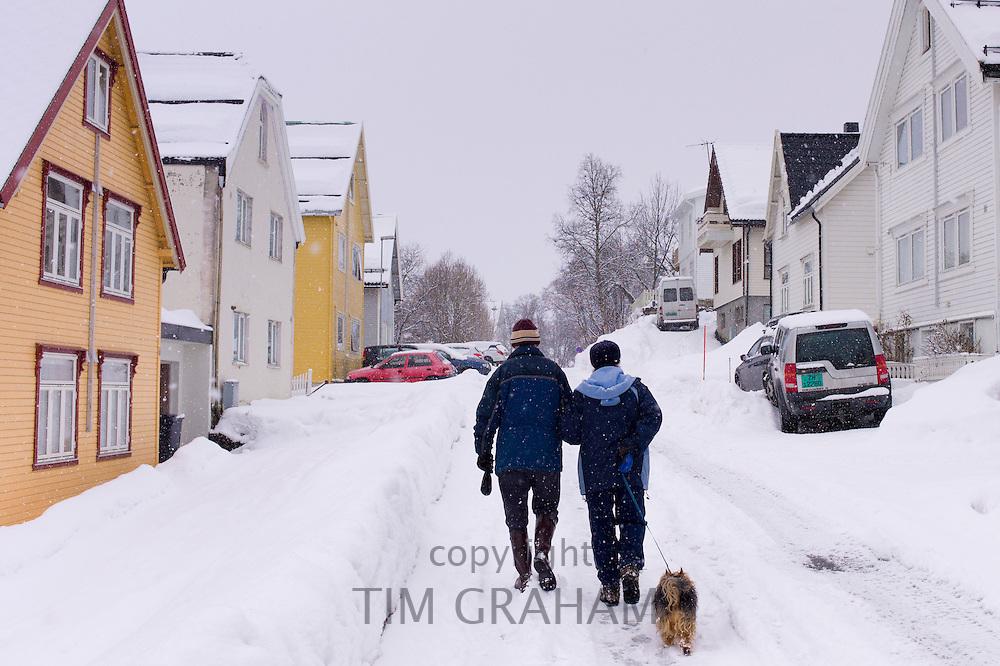 Street scene of couple walking their dog in Tromsoya, Tromso,  Arctic Circle in Northern Norway