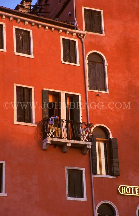 Windows and facade of a bright red-orange building in Verona, Italy.