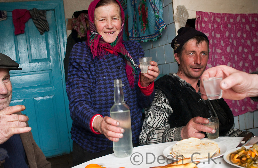 The Budgusain family in the village of Bereztsye on the Pripyat River in southern Belarus make a toast with homemade vodka before sitting down for a mid-day meal of traditional countryside dishes, including salo (thick slices of salted pork fat), sausages and cabbage on April 2, 2006.