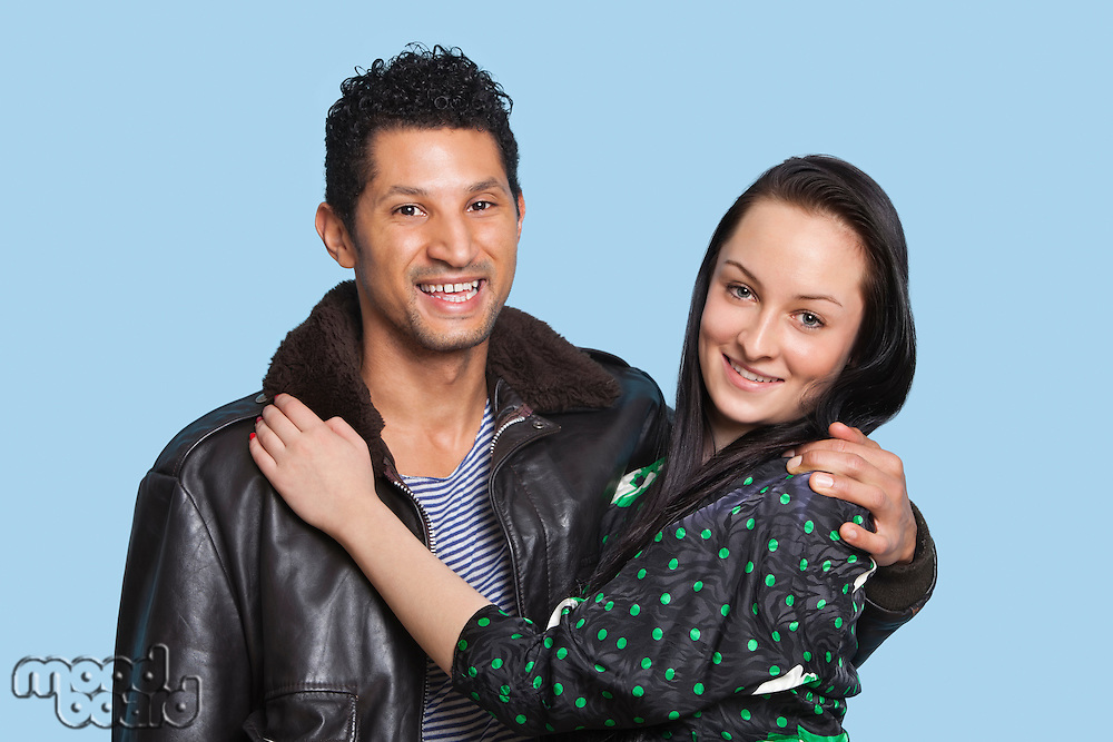Portrait of couple with arms around smiling against blue background