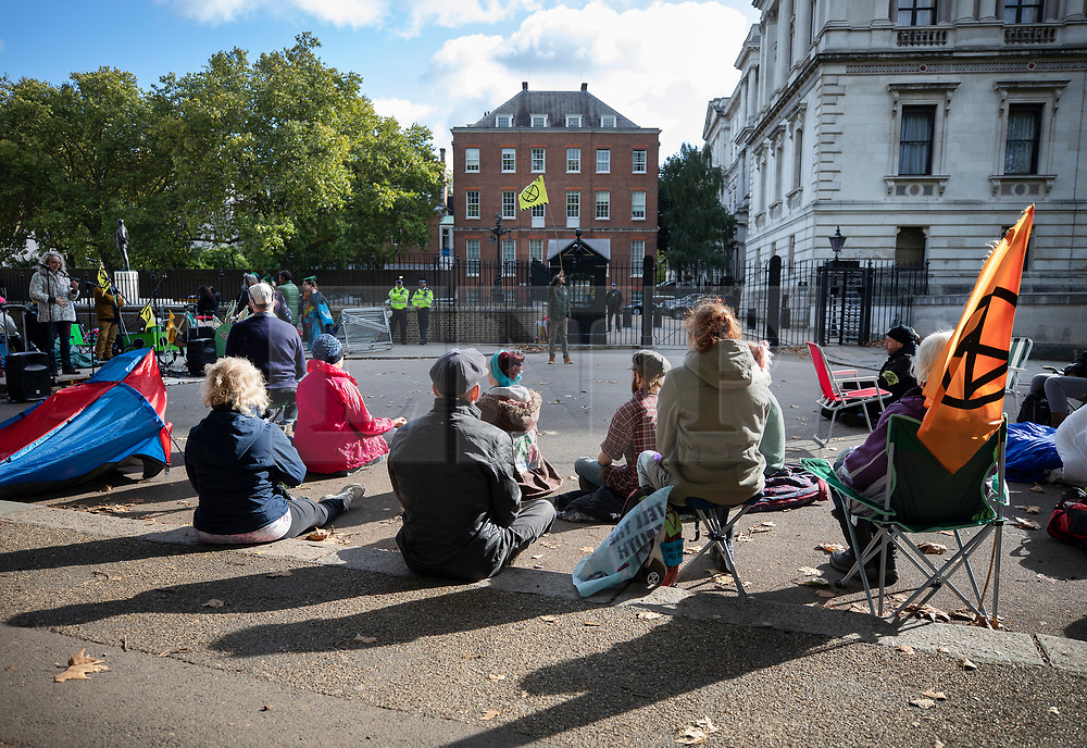 © Licensed to London News Pictures. 09/10/2019. London, UK. Extinction Rebellion activists takes part in a group meditation on Horse Guards Road in sight of the back of Downing Street (C) during a third day of protests in central London. The climate change group intend to blockade the Westminster area for two weeks to demand that the government takes immediate and decisive action on climate change. Photo credit: Peter Macdiarmid/LNP