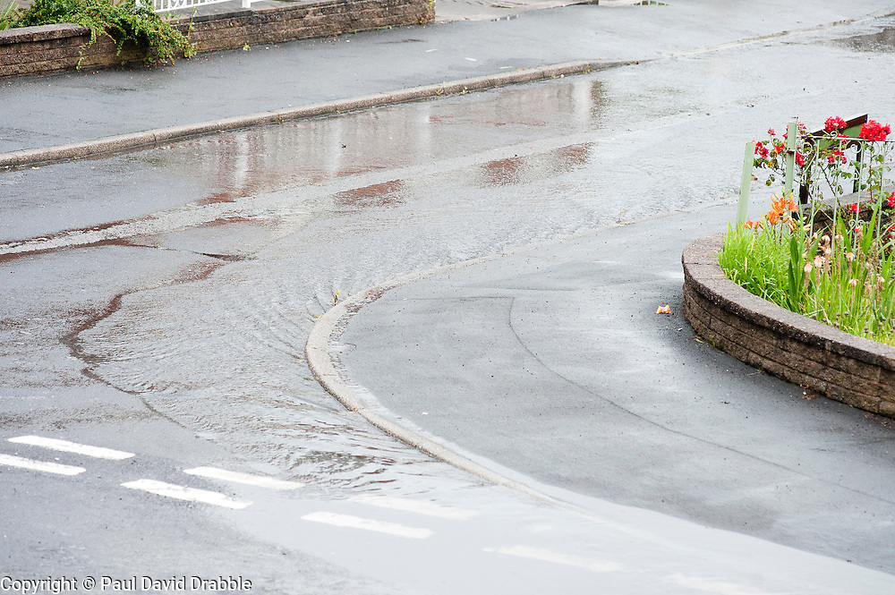 16:46 Ecclesfield Sheffield UK.The flash floodwater has made its way across Minster Road and is Pouring down Minster Close..5 July 2012.Image © Paul David Drabble