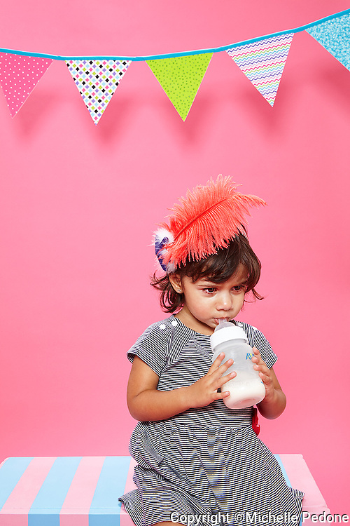 Little girl with an orange feather in her hair sitting on a pink and blue bench drinking a bottle of milk. Photographed at Photoville Photo Booth September 20, 2015
