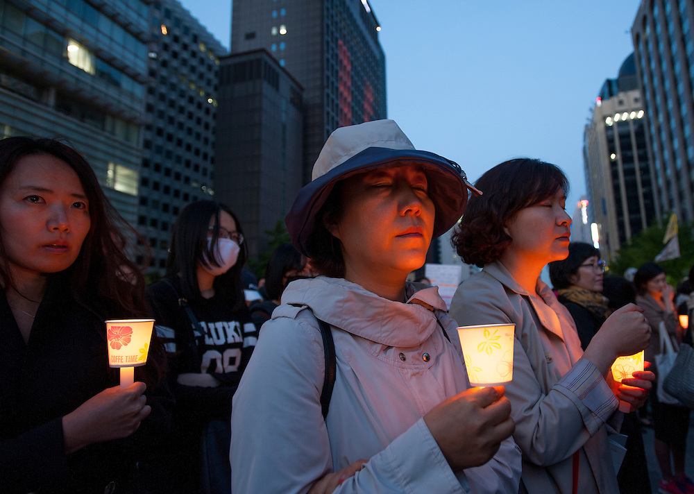 People hold candles and mourn for victims during a demonstration. About 5,000 people gathered in central Seoul to protest president Park Geun-hye and the government's response to the Sewol ferry sinking tragedy.