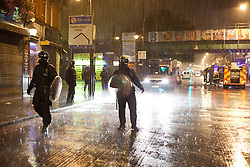 © Licensed to London News Pictures. 08/08/2011. LONDON, UK. Police stand stand in Brixton Road in pouring rain as firemen fight a fire deliberately started in the Brixton branch of Footlocker. Widespread looting had previously taken place in shops along the road with large amounts of people escaping with goods before the police arrived.  The looting came as violence again hit London for a second night. Photo credit: Matt Cetti-Roberts/LNP