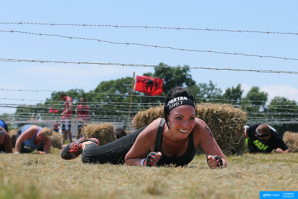 Stephanie Battista in action at the barbed wire crawl obstacle during the Reebok Spartan Race. Mohegan Sun, Uncasville, Connecticut, USA. 28th June 2014. Photo Tim Clayton