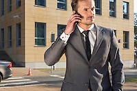 Young businessman using cell phone against office building