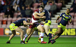 Wigan Warriors' Joe Green Wood is tackled by Wakefield Trinity's Jordan Crowther (left) and James Batchelor (right) during the Betfred Super League Super 8's match at the DW Stadium, Wigan.