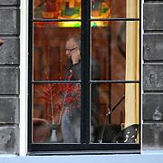 NLD/Amsterdam/20061220 - Cabaratier Youp van 't Hek telefonerend en kijkend uit zijn raam