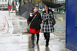 © under license to London News Pictures. 08/11/2010 A gust of wind catches a woman's umbrella as they walk along Hampstead Road London, she laughs with her friend.