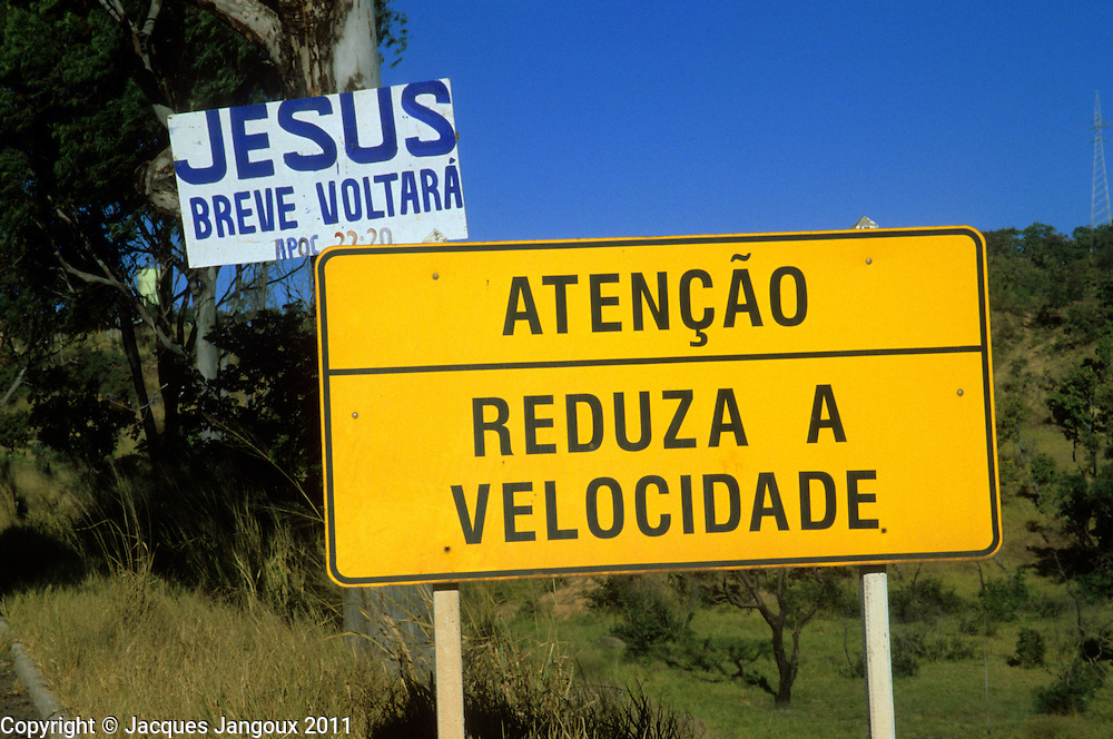 Humor: road signs: Warning: reduce speed; Jesus will come back soon. Highway between Goias State and Minas Gerais State, Brazil.