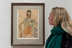 """© Licensed to London News Pictures. 31/10/2018. LONDON, UK. A staff member views """"The Cellist"""", 1910, by Egon Schiele. Preview of """"Klimt / Schiele:  Drawings from the Albertina Museum,Vienna"""" exhibition at the Royal Academy.  Over 100 works on paper are on display in an exhibition which marks the centenary of the deaths of the two most celebrated and pioneering figures of early twentieth-century art.  The show runs 4 November to 3 February 2019.  Photo credit: Stephen Chung/LNP"""