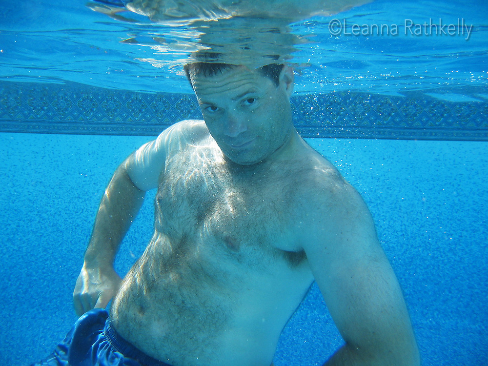 Man, 45-50, poses underwater at an outdoor pool
