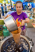 11 MAY 2013 - BANGKOK, THAILAND: A Yellow Shirt protester makes iced tea at the Yellow Shirt camp in Bangkok. A faction of the Yellow Shirts are camping at Sanam Luang, the royal parade ground in front of the Grand Palace, to show support for the Thai monarchy and the Thai Constitutional Court. The court has become a flash point in Thai politics because Red Shirts claim the court is biased against them and have been protesting against the court, calling for the justices' ouster and replacement with justices more open to the Red Shirts. The Yellow Shirt protest at Sanam Luang is calling for the Justices to remain on the court.    PHOTO BY JACK KURTZ