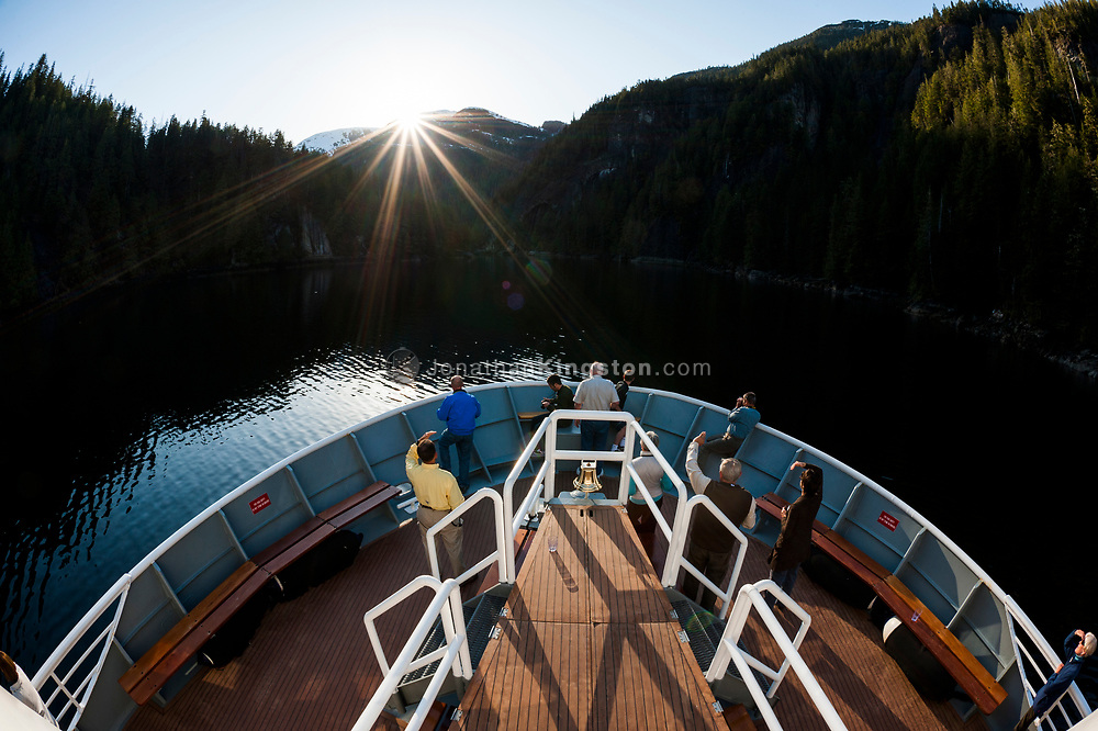 Passengers on the bow of a small cruise ship watch a sunburst.