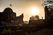 "29th January 2015, New Delhi, India. View of the ruins of Feroz Shah Kotla as believers move through them praying, making offerings and asking for their wishes to be granted by Djinns in the ruins of Feroz Shah Kotla in New Delhi, India on the 29th January 2015<br /> <br /> PHOTOGRAPH BY AND COPYRIGHT OF SIMON DE TREY-WHITE a photographer in delhi. + 91 98103 99809. Email:simon@simondetreywhite.com<br /> <br /> People have been coming to Firoz Shah Kotla to leave written notes and offerings for Djinns in the hopes of getting wishes granted since the late 1970's. Jinn, jann or djinn are supernatural creatures in Islamic mythology as well as pre-Islamic Arabian mythology. They are mentioned frequently in the Quran  and other Islamic texts and inhabit an unseen world called Djinnestan. In Islamic theology jinn are said to be creatures with free will, made from smokeless fire by Allah as humans were made of clay, among other things. According to the Quran, jinn have free will, and Iblīs abused this freedom in front of Allah by refusing to bow to Adam when Allah ordered angels and jinn to do so. For disobeying Allah, Iblīs was expelled from Paradise and called ""Shayṭān"" (Satan).They are usually invisible to humans, but humans do appear clearly to jinn, as they can possess them. Like humans, jinn will also be judged on the Day of Judgment and will be sent to Paradise or Hell according to their deeds. Feroz Shah Tughlaq (r. 1351–88), the Sultan of Delhi, established the fortified city of Ferozabad in 1354, as the new capital of the Delhi Sultanate, and included in it the site of the present Feroz Shah Kotla. Kotla literally means fortress or citadel."