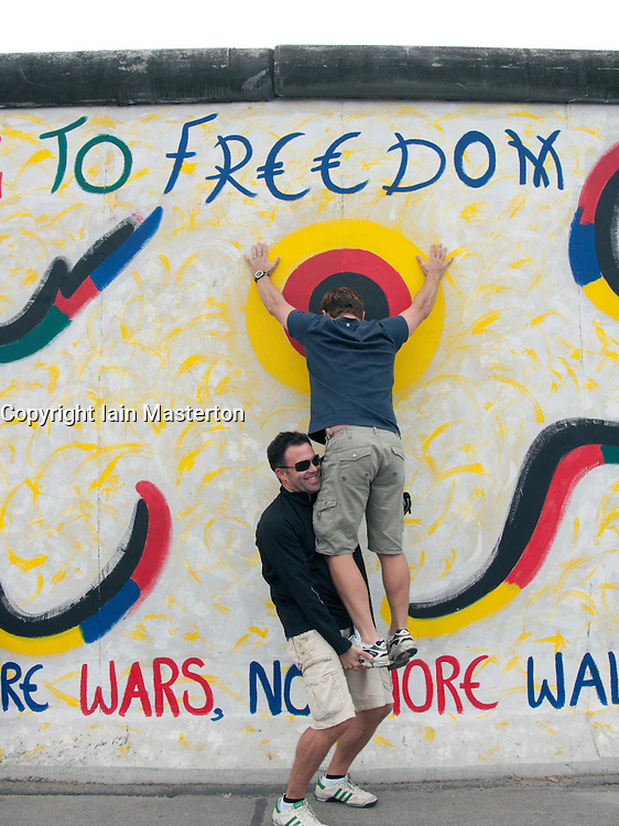Two tourists trying to act out an escape attempt over the Berlin Wall at East Side Gallery in Kreuzberg Berlin