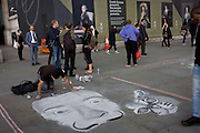 A street artist works on his pavement piece in front of Goya portraits, sponsored by Credit Suisse and advertised on a construction hoarding outside the National Portrait Gallery.