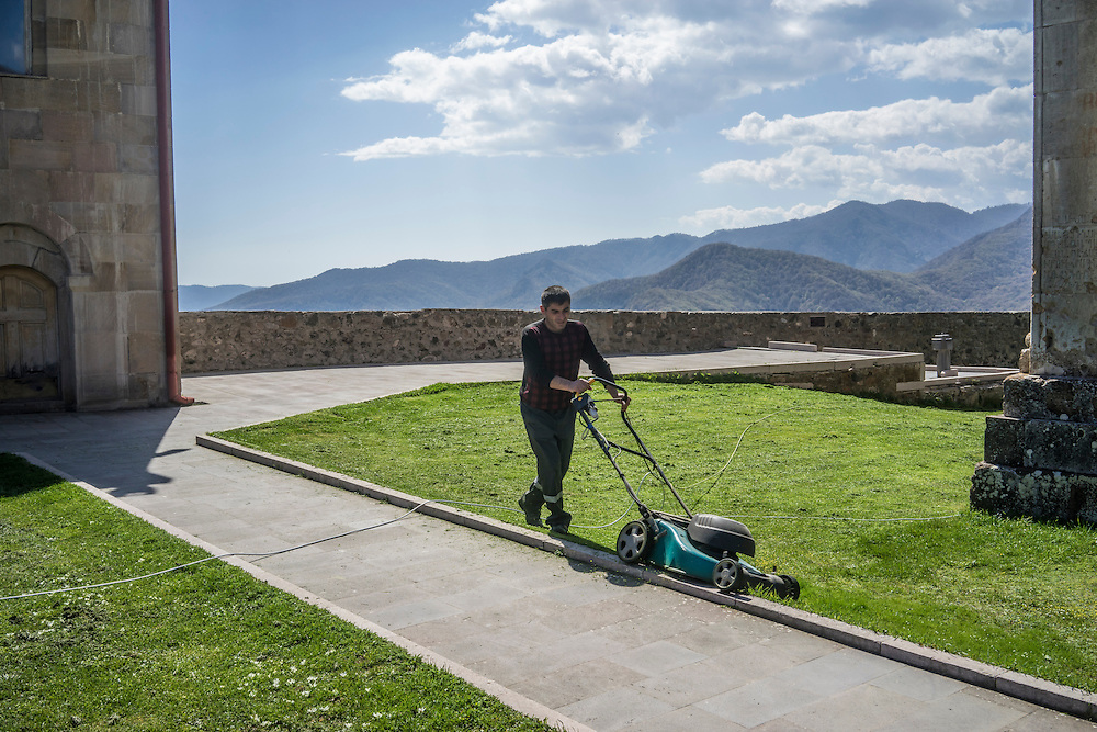 MARTAKERT, NAGORNO-KARABAKH - APRIL 18: A man cuts the grass at Gandzasar Monastery on April 18, 2015 in Martakert, Nagorno-Karabakh. Since signing a ceasefire in a war with Azerbaijan in 1994, Nagorno-Karabakh, officially part of Azerbaijan, has functioned as a self-declared independent republic and de facto part of Armenia, with hostilities along the line of contact between Nagorno-Karabakh and Azerbaijan occasionally flaring up and causing casualties. (Photo by Brendan Hoffman/Getty Images) *** Local Caption ***
