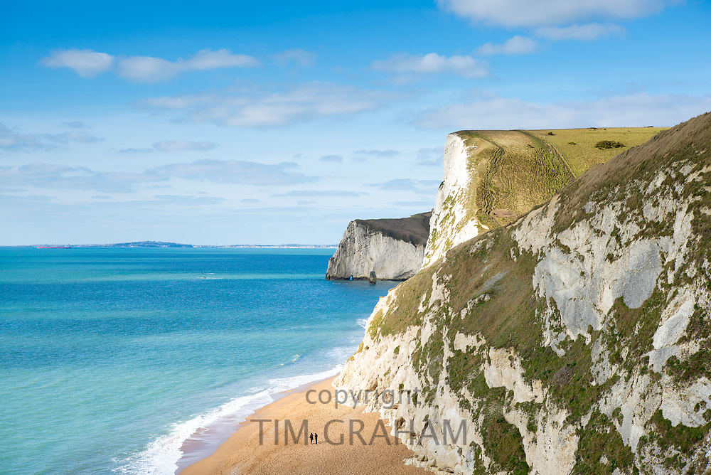 Tiny figures on the beach by limestone cliffs of the Jurassic coast towards Bat's Head near Lulworth, Wareham, Dorset, UK