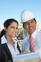 Businessman in hardhat showing clipboard to businesswoman with earpiece
