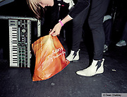 Emily, putting equipment into a Sainsburys bag after a gig, The Junk Club, Southend, UK 2006