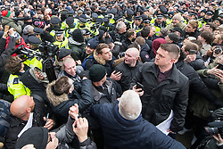 "© Licensed to London News Pictures . 18/03/2018 . London , UK . TOMMY ROBINSON (right) and supporters are separated from those opposed to his speech by a line of police as Robinson delivers his speech to the crowd . 1000s including supports of alt-right groups such as Generation Identity and the Football Lads Alliance , at Speakers' Corner in Hyde Park where Tommy Robinson reads a speech by Generation Identity campaigner Martin Sellner . Along with Brittany Pettibone , Sellner was due to deliver the speech last week but the pair were arrested and detained by police when they arrived in the UK , forcing them to cancel an appearance at a UKIP "" Young Independence "" youth event , which in turn was reportedly cancelled amid security concerns . Photo credit: Joel Goodman/LNP"