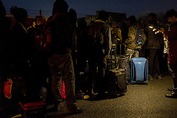 October 24, 2016 - Calais, France - Refugees arrive early and wait in front of the hangar distribution of refugees with their luggage in Calais, France on october 24, 2016. The dismantling of the jungle began Monday morning. Refugees come accompanied by the associations to the starting center ''C.A.O.''. Police frames the device. More than 850 press credentials were distributed. (Credit Image: © Julien Pitinome/NurPhoto via ZUMA Press)