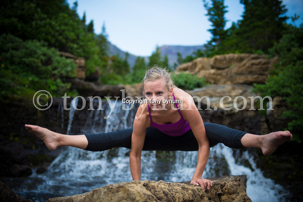 woman in small steam on rock near waterfall doing yoga hand balance