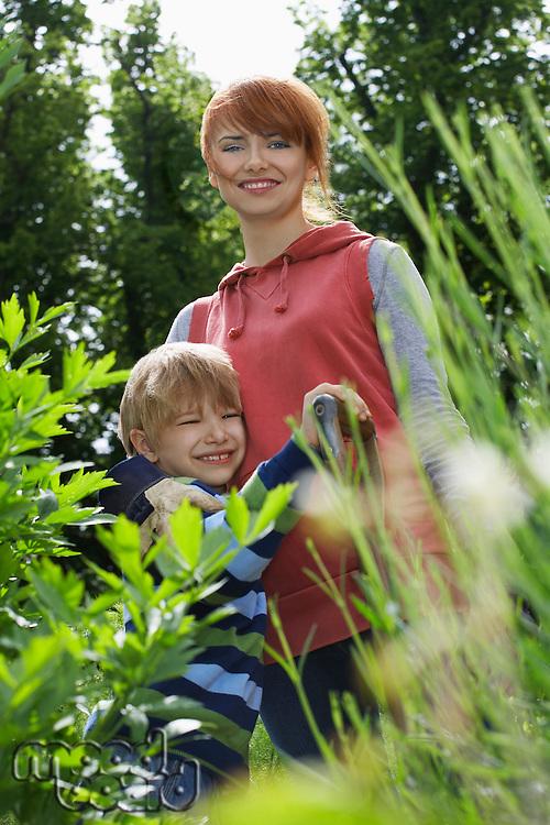 Mother embracing son (5-6) in garden portrait