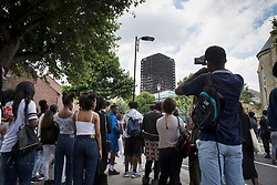© Licensed to London News Pictures. 18/06/2017. London, UK. People look at the remains of the burnt out Grenfell tower block . The blaze engulfed the 27-storey building killing dozens - with 34 people still in hospital, many of whom are in critical condition. The fire brigade say that they don't expect to find anyone else alive. Photo credit: Peter Macdiarmid/LNP