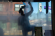 Zach Kratochvil, sophomore studying marketing and management, turns to shadows as he applies a white coat of paint onto a window of Pita Pit in Manhattan, Kansas' Aggieville on October 13, 2015. The painting of business windows by greek and student organizations in Aggieville is a long standing Homecoming tradition at Kansas State.