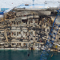 ISOLA DEL GIGLIO, ITALY - SEPTEMBER 17:  The wreckage of the Costa Concordia with the previously submerged part is seen after the succesful operation of parbuckling on September 17, 2013 in Isola del Giglio, Italy. After the successful operation the work on the ship will re start once again with plans to be towed away in late spring 2014.  (Photo by Marco Secchi/Getty Images)