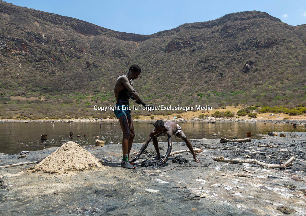 EL SOD: THE SALT OF LIFE<br />  <br />  El Sod, the House Of Salt, is a village located 90 km from Yabelo, the capital of Borana people in South Ethiopia. It stands on the edge of an extinct volcano wide of 1,8 km diameter, with a salted lake in the crater. For centuries, men dive into the lake to collect the salt and sell it across Ethiopia, Somalia and Kenya<br /> <br />  It takes 1 hour on a narrow path to go down the 2,5 km from the village to the lake, 340 meters lower. The best view on the crater can be spotted from the recently built mosque.<br /> Every miner works as a free lance, independent from any company or boss. Most of the time divers are naked, the salted water being so agressive that it destroys everything, including clothes and shoes.<br />  Miners try to protect their nose and ears with plugs made of soil wrapped in plastic bags. There's no protection for the eyes: many suffer heavily from blindness.<br />  When the weather is good after rains (Borana wait for it for months since the area suffers from drought) more than 200 men dive into the lake. More and more children are joining for the families to get some extra revenue. The parents are aware of the dangers but they don't have any choice if they want to survive.<br /> <br /> Photo Shows:  Volcano crater where Borana tribe men dive to collect salt, Oromia, El Sod, Ethiopia<br /> ©Eric lafforgue/Exclusivepix Media