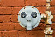 Pipe and control with face against brick wall, Pearl District, Portland, Oregon.