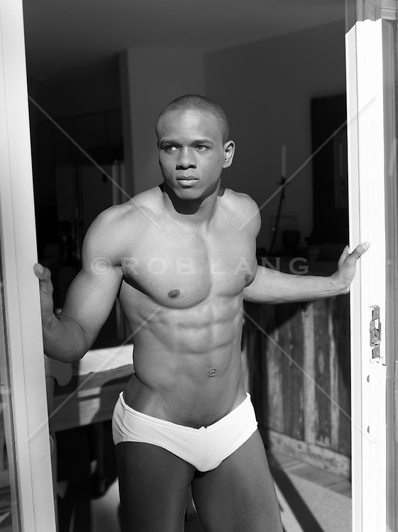 muscular man in white briefs standing in a doorway at home