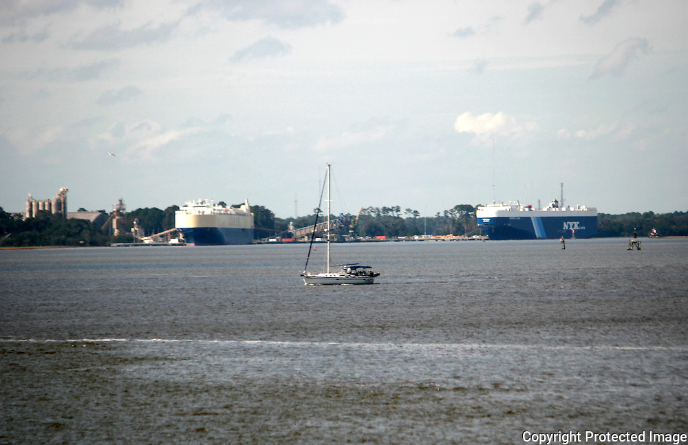 A sail boat crossing the bay in front of two large cargo ships being loaded with cargo at a Brunswick Georgia Port.
