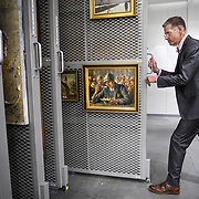 BOWIE, MD - MAY3: Travis Roxlau, director of Collection Services, opens an art vault containing paintings by Holocaust survivors at the U.S. Holocaust Memorial Museum's David and Fela Shapell Family Collections, Conservation and Research Center in Bowie, MD, May 3, 2017. The 80,000-square-foot Shapell Center is a state-of-the-art facility that will house the collection of record of the Holocaust, including historical artifacts, documents, photographs, film and other objects related to the Holocaust. (Photo by Evelyn Hockstein/For The Washington Post)