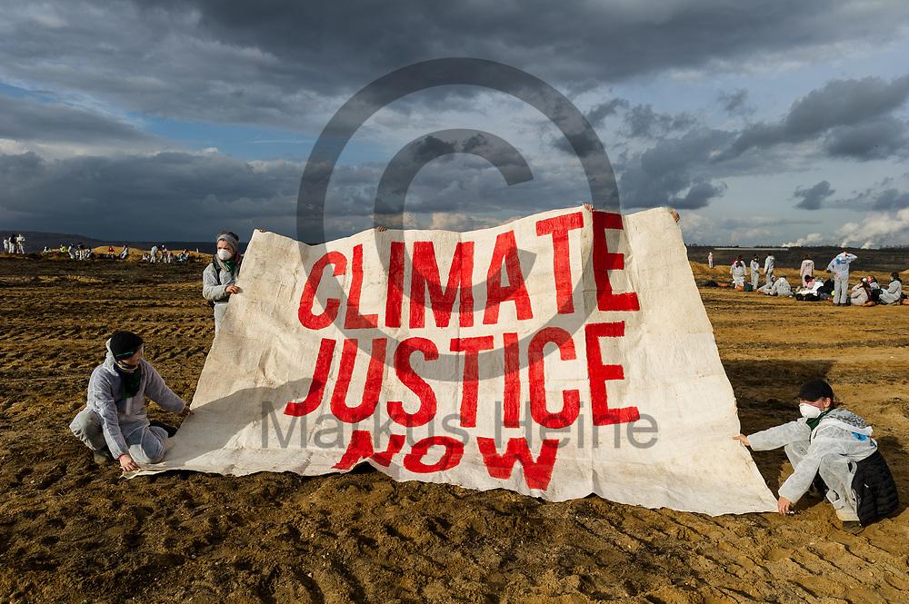 Deutschland, Elsdorf - 05.11.2017<br /> <br /> &quot;Climate justice now&quot; steht auf einem Banner der Aktivisten in der Grube. Circa 2500 Aktivisten drangen in die Grube des Braunkohle Tagebau Hambach ein um mit der Aktion f&uuml;r einen sofortigen Kohleausstieg zu protestieren. Die Aktion fand im Rahmen von Protesten im Vorfeld der UN-Klimakonferenz in Bonn statt.<br /> <br /> Germany, Elsdorf - 05.11.2017<br /> <br /> &quot;Climate justice now&quot; is written on a banner of activists in the coal pit. Approximately 2500 activists invaded the pit of the lignite opencast mine Hambach to protest for an immediate coal exit. The action took place during protests prior to to the UN Climate Change Conference in Bonn.<br /> <br />  Foto: Markus Heine<br /> <br /> ------------------------------<br /> <br /> Ver&ouml;ffentlichung nur mit Fotografennennung, sowie gegen Honorar und Belegexemplar.<br /> <br /> Bankverbindung:<br /> IBAN: DE65660908000004437497<br /> BIC CODE: GENODE61BBB<br /> Badische Beamten Bank Karlsruhe<br /> <br /> USt-IdNr: DE291853306<br /> <br /> Please note:<br /> All rights reserved! Don't publish without copyright!<br /> <br /> Stand: 11.2017<br /> <br /> ------------------------------