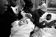 83777  -----  Nikosha Jackson, second from right, pokes her sister Donesha Jackson's stomach, far right, beside their friends Kassius Hollins, 15, Katasia Hollins, 16, Dasha Terry, 16, holding Camron Kelley, 3 months, an hour after Donesha Jackson, 17, gave birth to a baby boy Quintel Wilson, at 7lbs 2oz, at Presbyterian Hospital in Dallas, TX on February 28, 2005..Pastor Rock has spent the past three years fighting race, poverty  and violence at Sugar Hill, the poorest of the poor living in public housing in Texas' richest county, Collin County. Originating in 1969, the McKinney apartment complex rose next to an old cotton field, with 100 units that would battle decades of economic annd racial isolation, squalor, criminal neglect, crack cocaine and bureaucratic equivocation supported by millions of taxpayer dollars.