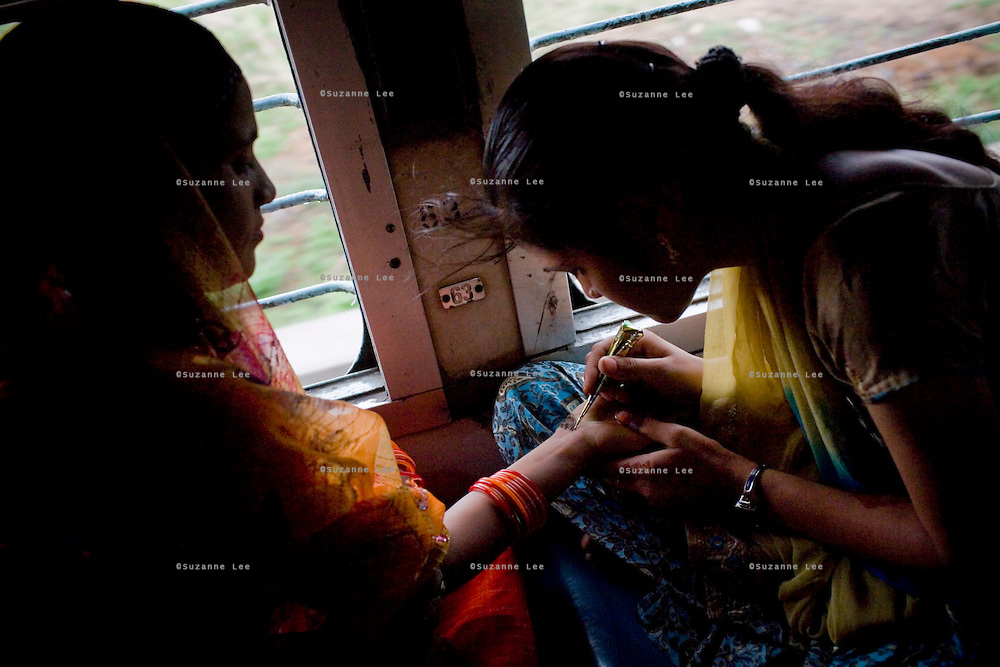 Nisha Goswami aged 18, draws menhdi on her friend, Sulochna Lakhera's (aged 32) palm to pass time while the Himsagar passes through Andhra Pradesh on 8th July 2009.. .6318 / Himsagar Express, India's longest single train journey, spanning 3720 kms, going from the mountains (Hima) to the seas (Sagar), from Jammu and Kashmir state of the Indian Himalayas to Kanyakumari, which is the southern most tip of India...Photo by Suzanne Lee / for The National