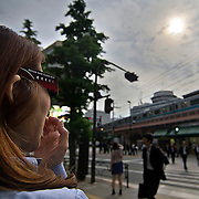 A woman views the annular solar eclipse over Yurakucho Station in Tokyo, Monday, May 21, 2012. (Albert Siegel)
