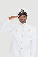 Portrait of a young African American US Navy officer saluting over gray background
